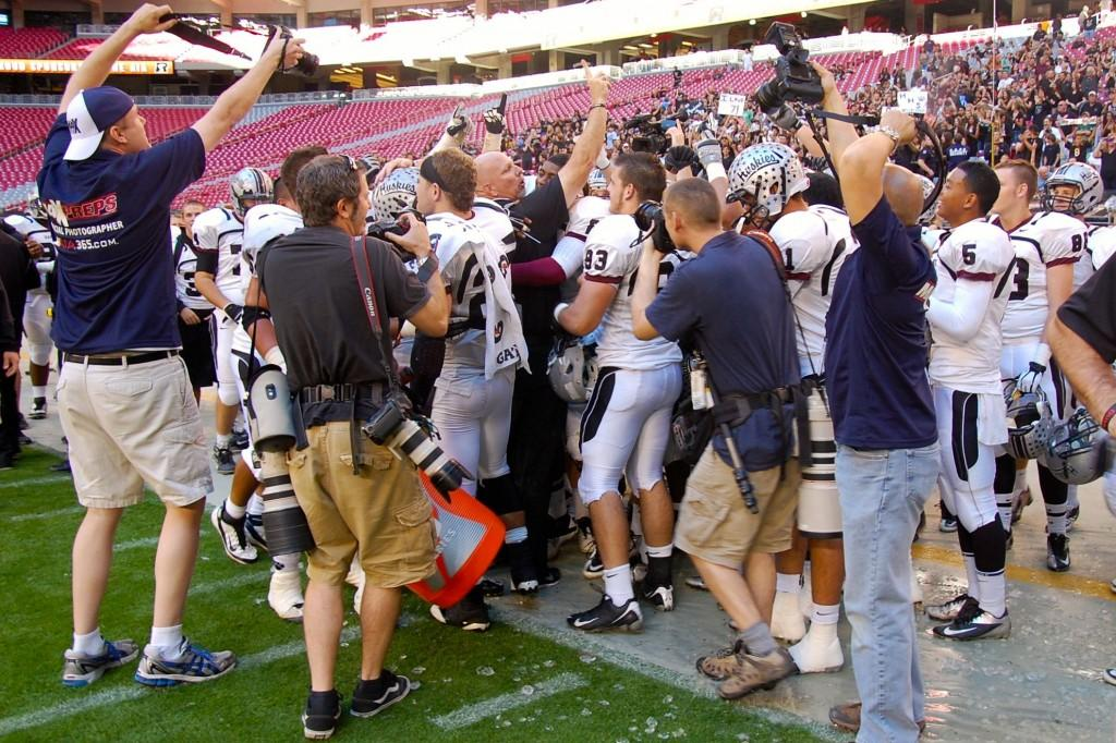 Players and coaches on the sidelines celebrate as the game reaches its end.