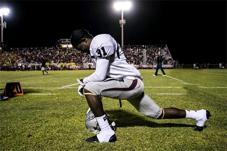Senior Jerrion Acles takes a knee during an away game.
